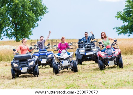 Friends driving off-road with quad bike or ATV - stock photo