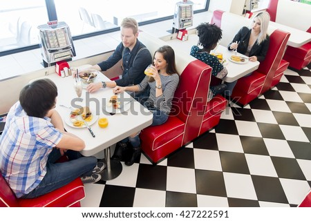 Friends eating at the table in the diner - stock photo