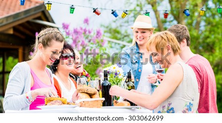 Friends eating bbq sausage and meat at garden or grill party - stock photo