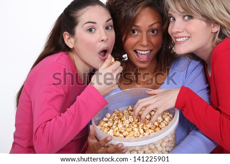 Friends eating caramel popcorn together - stock photo