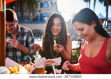 friends eating french fries and hamburgers together at outdoor restaurant under summer sun - stock photo