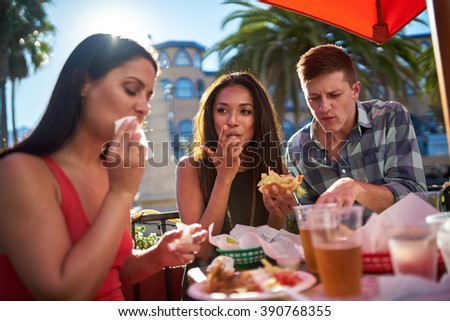 friends eating meal together in sunny california