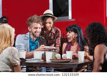 Friends eating out and looking over text messages - stock photo
