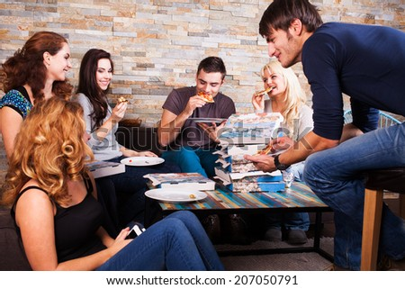 friends eating pizza together  - stock photo