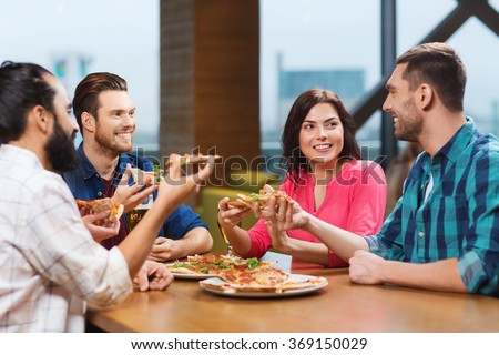 friends eating pizza with beer at restaurant - stock photo