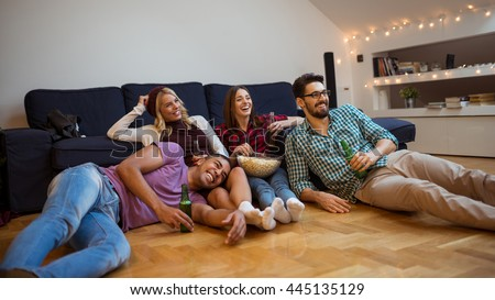 Friends eating popcorn and watching movies together. - stock photo