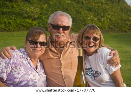 Friends enjoy an outdoor Picnic and a Bottle of Wine - stock photo