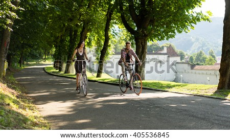 friends enjoy the bike in an alley with trees on a summer day on the outskirts of the medieval city - stock photo