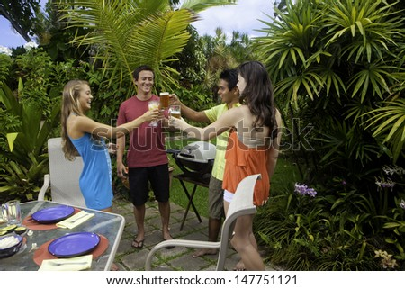 friends enjoying a barbecue lunch in a tropical garden - stock photo
