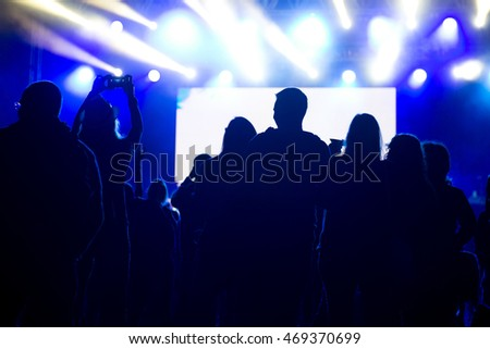 Friends enjoying concert, people dancing at a party, silhouettes