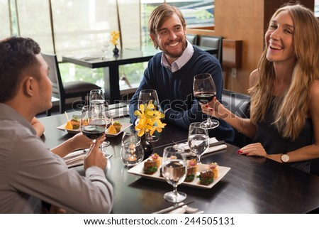 Friends enjoying meal in a restaurant, selective focus - stock photo