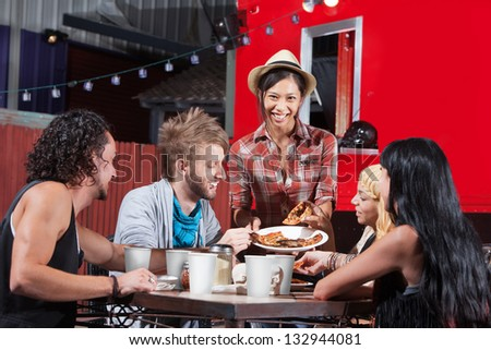 Friends enjoying pizza for late night snack - stock photo