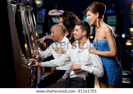 friends enjoying playing the slot machine at the casino - stock photo