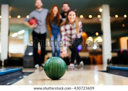 Friends enjoying recreational  bowling at club - stock photo