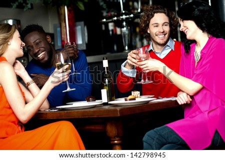 Friends enjoying snacks with drinks in a bar. - stock photo