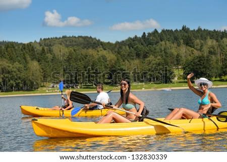 Friends enjoying summertime kayaking on river holiday free time - stock photo