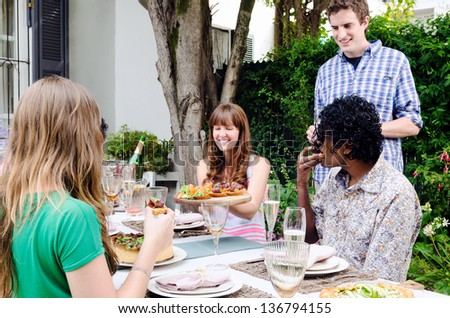 Friends enjoying themselves and having fun at a party with food and alcohol, a casual lunch get together in a garden - stock photo