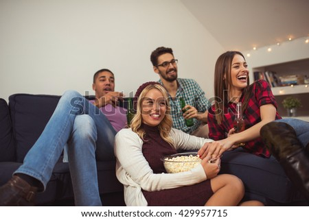 Friends enjoying watching movies at home. - stock photo