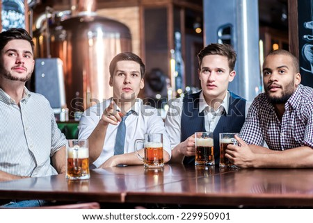 Friends fans drinking beer and watching TV at the bar. Four friends sitting at the table and holding glasses of beer in their hands. Friends having fun together - stock photo