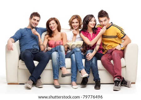 friends feeding popcorn to each other while sitting couch - stock photo