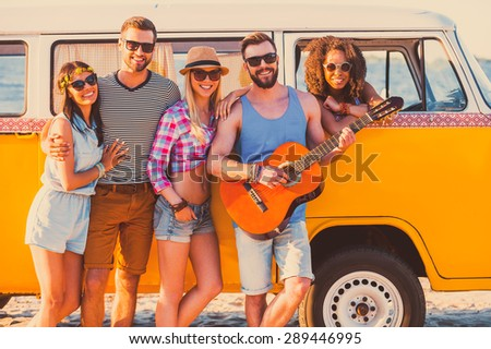 Friends forever. Group of young cheerful people standing near their retro minivan and smiling  - stock photo