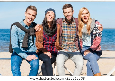 Friends forever. Group of young happy people bonding to each other and smiling while sitting at the riverbank - stock photo