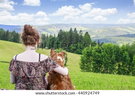 Friends forever: woman and her lovely dog sitting in the meadow. Beautiful landscape with trees and hills.  - stock photo