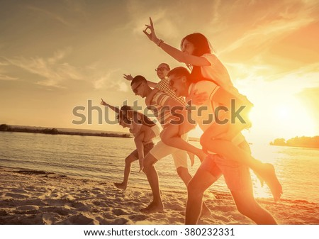 Friends fun on the beach under sunset sunlight. - stock photo