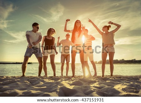 Friends funny dance on the beach under sunset sunlight.