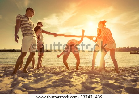 Friends funny game on the beach under sunset sunlight. - stock photo