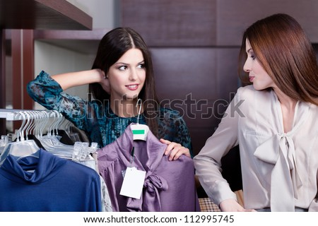 Friends give pieces of advice to each other concerning the clothes - stock photo