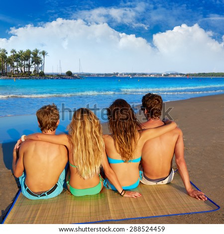 friends group couples sitting in beach sand rear view Alcudia Mallorca photo mount - stock photo