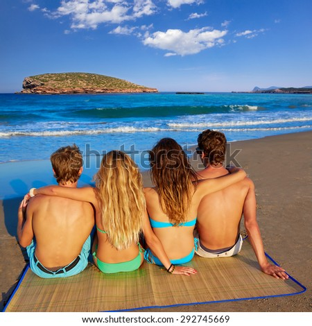 friends group couples sitting in beach sand rear view Ibiza photo mount - stock photo