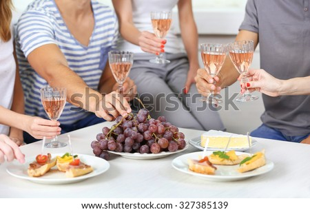 Friends hands with glasses of wine and snacks, close up