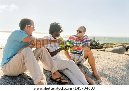 Friends hanging out by the beach drinking beers, enjoying the sunny afternoon - stock photo