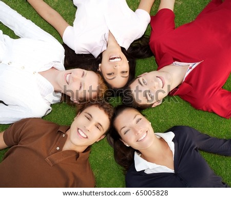 friends happy group in circle heads together on green grass outdoor - stock photo