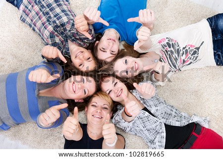friends happy group in circle together on floor, showing thumbs up - stock photo