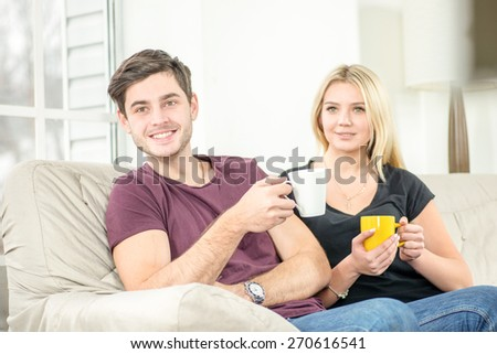 Friends have fun together. Cheerful young people sitting on the couch and drinking tea or coffee while cuddling fun and make self on the tablet. People keep smiling and laughing with tablet - stock photo