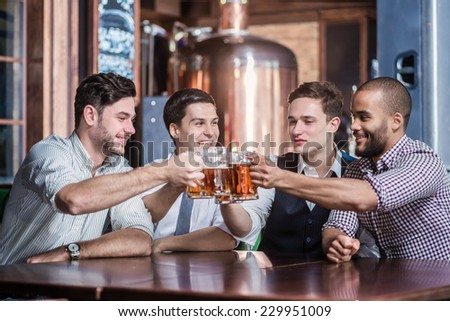 Friends have met at the bar. Four friends sitting at the table clink glasses with beer in their hands. Friends having fun together - stock photo