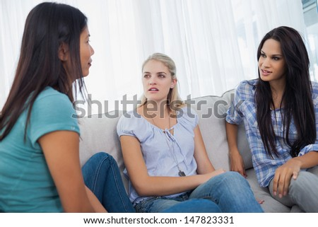 Friends having a conversation together at home on the couch - stock photo