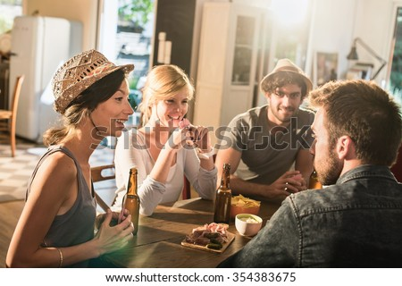 Friends having a drink and playing poker on a sunny evening. They are sitting at a wooden table in a cozy house with beers and tortilla chips. They are smiling, wearing casual clothes and hats.