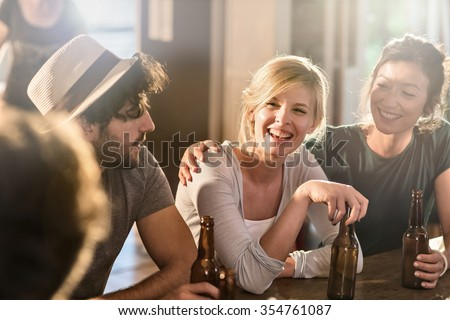 Friends having a drinks on a sunny evening in a cozy house. They are sitting at a wooden table with beers. They are wearing casual clothes. Focus on a gorgeous blonde girl touching her bottle.
