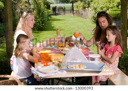 Friends having a picnic outdoors on a summer's day - stock photo