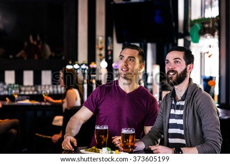 Friends having a pint and watching tv in a bar - stock photo