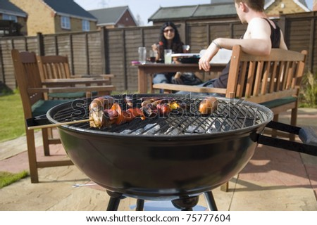 Friends having barbeque in back garden - stock photo