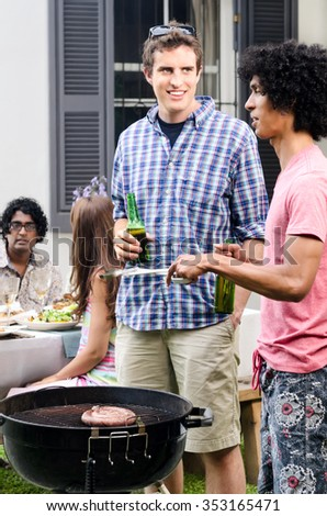 Friends having beers around a barbecue bbq at a outdoor garden party, with meat on the grill