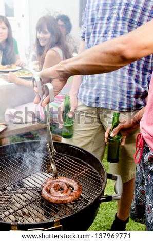 Friends having beers by the bbq at a party, with meat smoking on the hot grill - stock photo