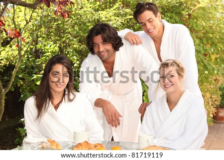Friends having breakfast together outside - stock photo