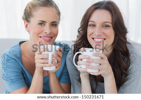 Friends having coffee and looking at camera sitting on the couch - stock photo