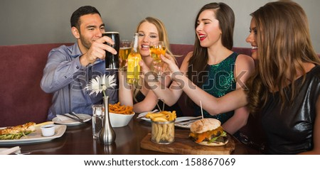 Friends having dinner together and clinking glasses in restaurant - stock photo